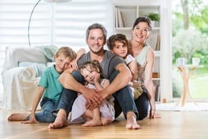 Family at home sitting together on their hardwood floor